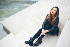 Beautiful young woman is sitting on the concrete steps. Royalty Free Stock Image