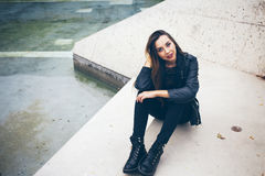 Beautiful young woman is sitting on the concrete steps. Student in alternative style clothes - black leather jacket and big boots. Copy-space area for your Royalty Free Stock Photos