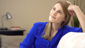 Beautiful young woman sitting on a couch and dreaming of something good and positive. Enjoying life. stock footage