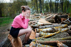 Beautiful young woman sitting and covering his face with his hands, on stack of felled tree trunks in the forest. Beautiful young woman sitting on stack of Royalty Free Stock Images