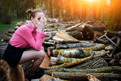 Beautiful young woman sitting and covering his face with his hands, on stack of felled tree trunks in the forest. Beautiful young woman sitting on stack of Royalty Free Stock Photography