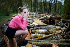 Beautiful young woman sitting and covering his face with his hands, on stack of felled tree trunks in the forest. Beautiful young woman sitting on stack of Stock Photo