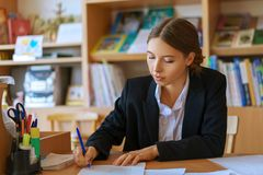 Beautiful young woman sitting at Desk with papers royalty free stock photography