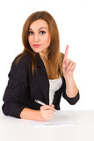 Beautiful young woman sitting at the desk and pointing up. Royalty Free Stock Photo