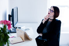 Beautiful young woman sitting at the desk and thinking in the co royalty free stock images