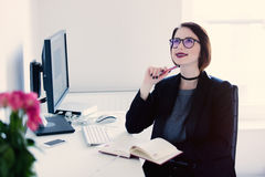 Beautiful young woman sitting at the desk and thinking in the co stock images