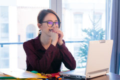 beautiful young woman sitting at the desk and thinking about something in her office stock images