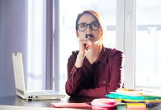 beautiful young woman sitting at the desk and thinking about something with pen in her hand in her office stock photography