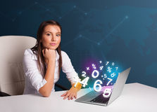 Beautiful young woman sitting at desk and typing on laptop with Stock Photo