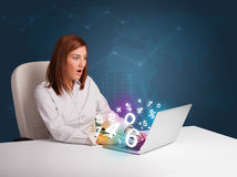 Beautiful young woman sitting at desk and typing on laptop with Royalty Free Stock Photography