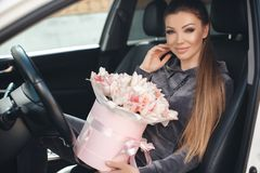 Beautiful young woman, sitting on the driver`s seat in a car with a pink box full of tender, white, with a pink edging of tult-col. Beautiful young woman,sitting stock images