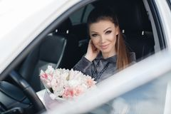 Beautiful young woman, sitting on the driver`s seat in a car with a pink box full of tender, white, with a pink edging of tult-col. Beautiful young woman,sitting royalty free stock image