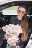 Beautiful young woman, sitting on the driver`s seat in a car with a pink box full of tender, white, with a pink edging of tult-col. Beautiful young woman,sitting royalty free stock photo