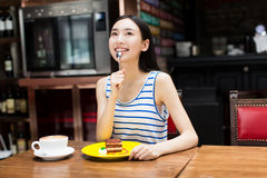 Beautiful young woman sitting and eating cake Stock Photo