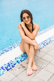 Beautiful young woman sitting on edge of swimming pool. summer vocation Stock Photo