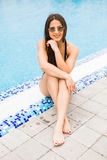 Beautiful young woman sitting on edge of swimming pool. summer vocation Royalty Free Stock Photo