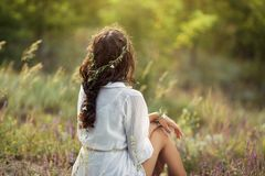 Beautiful young woman sitting in a wheat field in the summer sunset. Beauty and summer concept royalty free stock images
