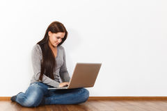 Beautiful young woman sitting on floor with laptop Royalty Free Stock Photography