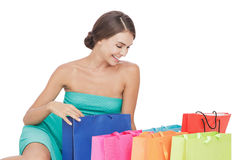 Beautiful young woman sitting on the floor next to her shopping Stock Image