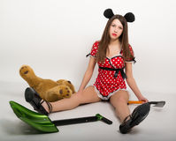 Beautiful young woman sitting on the floor in a short dress with polka dots, next to it is a shovel and a teddy bear in Royalty Free Stock Photos