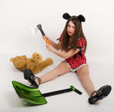 Beautiful young woman sitting on the floor in a short dress with polka dots, next to it is a shovel and a teddy bear in. Her hand holding the ax royalty free stock photos