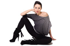 Beautiful young woman sitting on the floor. White background Royalty Free Stock Photo