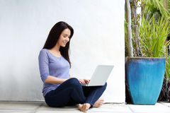 Beautiful young woman sitting on floor and working with laptop Royalty Free Stock Photo