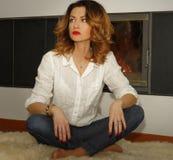 Beautiful young woman sitting on fur carpet near fireplace Stock Photo