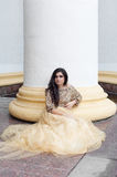 Beautiful young woman is sitting. Beautiful young woman in gold dress is sitting in front of a column Royalty Free Stock Image