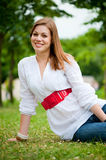 Beautiful young woman sitting at the grass Royalty Free Stock Photos