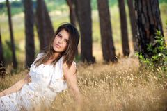 Beautiful young woman sitting in grass in the countryside Stock Photo