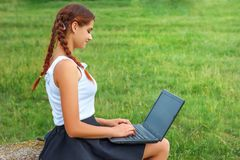 Beautiful young woman sitting on grass with laptop royalty free stock photo