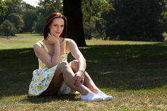 Beautiful young woman sitting on grass in park royalty free stock image