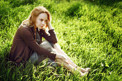 Beautiful young woman is sitting in the grass. Rel Royalty Free Stock Photography