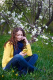 Beautiful young woman sitting on grass with a smartphone Royalty Free Stock Photos