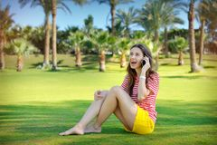 Beautiful young woman sitting on a green lawn and talking on a cell phone Stock Image