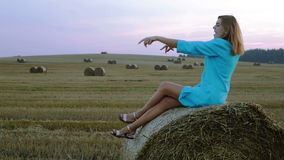 Beautiful young woman sitting on a haystack and dancing. stock footage