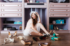 Beautiful young woman sitting in her closet. Beautiful young smiling woman in her closet wearing hat royalty free stock photos