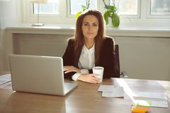 Beautiful young woman sitting in her home office. Attractive young businesswoman sitting at her desk with laptop looking at camera. Beautiful woman sitting at stock photos