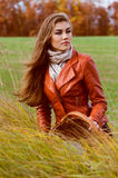 Beautiful young woman sitting in high grass on windy autumn day