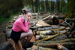 Beautiful young woman sitting and holding his head with his hands, on stack of felled tree trunks in the forest Stock Photos