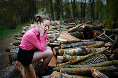 Beautiful young woman sitting and holding his head with his hands, on stack of felled tree trunks in the forest. Beautiful young woman sitting on stack of felled Stock Photos