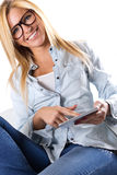 Beautiful young woman sitting at home with digital tablet Royalty Free Stock Photos