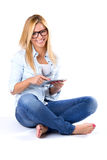 Beautiful young woman sitting at home with digital tablet Royalty Free Stock Photography