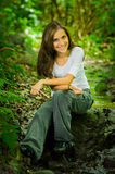Beautiful young woman sitting in the jungle Royalty Free Stock Images