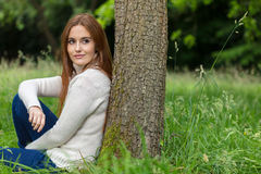 Beautiful Young Woman Sitting Leaning Against Tree Stock Photos