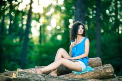 Beautiful Young Woman sitting on log posing Stock Images