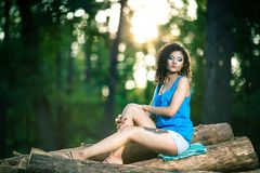 Beautiful Young Woman sitting on log posing Royalty Free Stock Photography