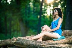 Beautiful Young Woman sitting on log posing Stock Photography