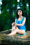 Beautiful Young Woman sitting on log posing Royalty Free Stock Photo